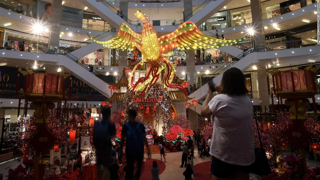 Visitors walk past a giant rooster installation at a shopping mall in Kuala Lumpur, Malaysia, on Wednesday, January 11.