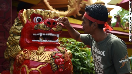 "A worker paints a statue at a Chinese temple ahead of the Lunar New Year festival in Denpasar, on Indonesia's Bali island on January 23, 2017. Indonesian-Chinese are preparing to celebrate the Lunar New Year or ""Spring Festival, which falls on January 28 this year, for the start of the Year of the Rooster."