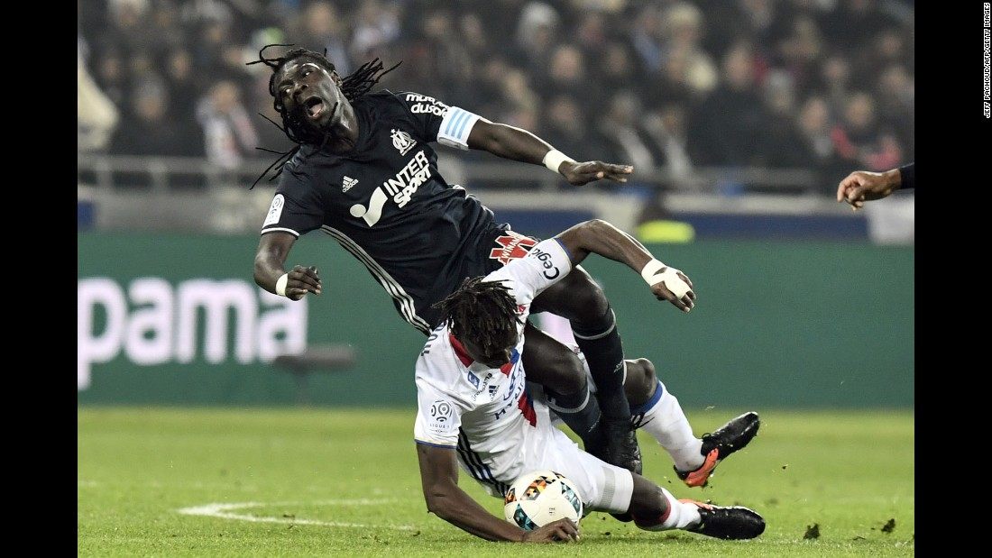 Marseille forward Bafetembi Gomis, top, is tackled by Lyon defender Mapou Yanga-Mbiwa during a French league match on Sunday, January 22.
