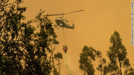 A firefighter helicopter helps try to put out a forest fire in Pumanque, 140 km south of Santiago on January 21, 2017.  The Chilean government declared a state of emergency in several central areas due to forest fires that have destroyed more than 35,000 hectares of woods so far. / AFP / MARTIN BERNETTI        (Photo credit should read MARTIN BERNETTI/AFP/Getty Images)
