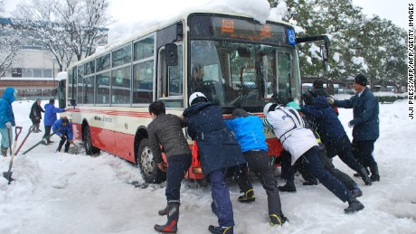 People push a bus stuck in the heavy snow in Tottori, western Japan, on January 24, 2017. Heavy snow hit western Japan, leaving some 100 cars stranded on January 24, prompting the Tottori prefecture governor to request help from the military. / AFP / JIJI PRESS / JIJI PRESS / Japan OUT        (Photo credit should read JIJI PRESS/AFP/Getty Images)