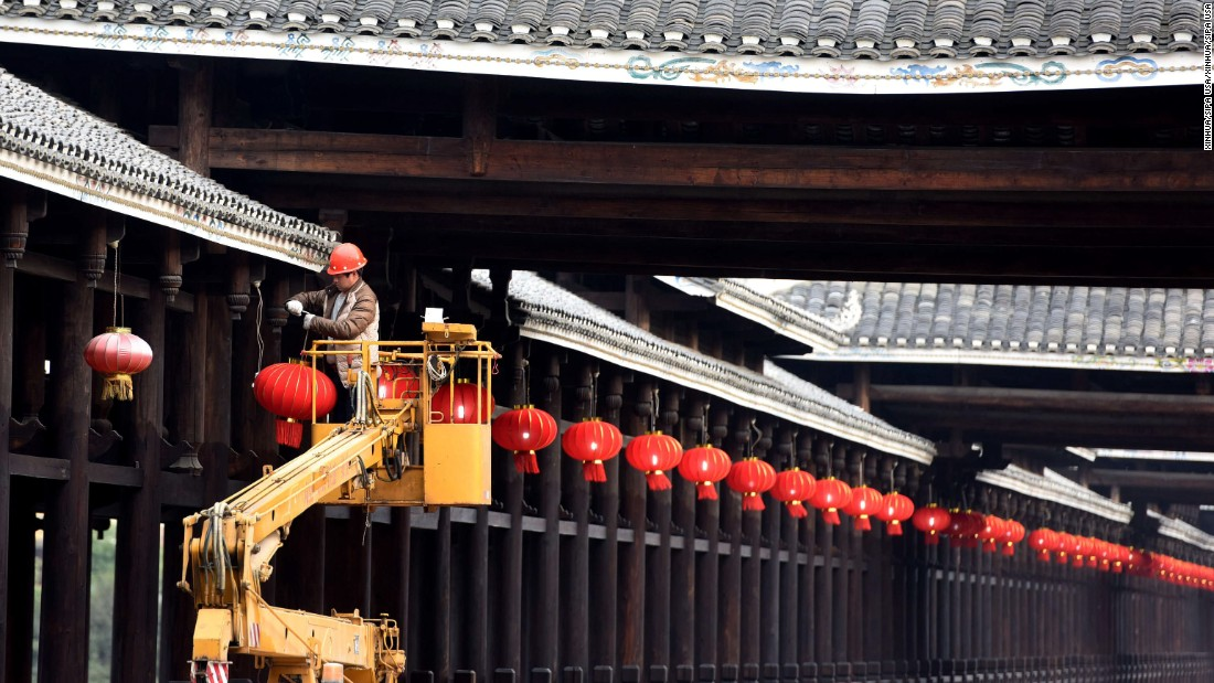 A worker hangs red lanterns on a bridge in China's Sanjiang Dong Autonomous County on Monday, January 23.