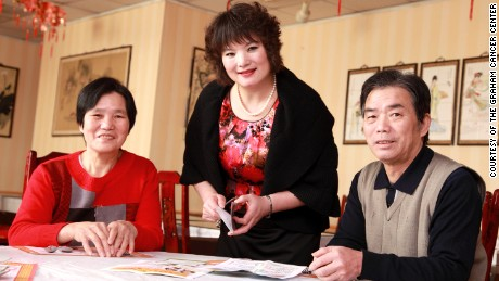 Outreach coordinator Xiangfen Gu, center, visits restaurant owners Qiu qi Li, left, and Mei zhen Dong on behalf of the Graham Cancer Center to stress the need for cancer screenings.
