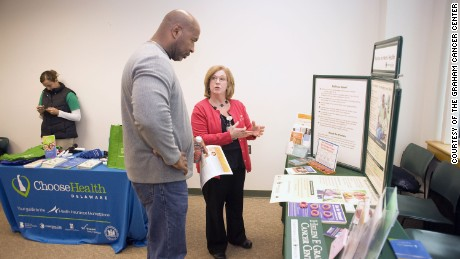 Cancer screening nurse navigator Charlene Marinelli of the Graham Cancer Center talks about colorectal cancer with a participant at an event geared toward men of color.