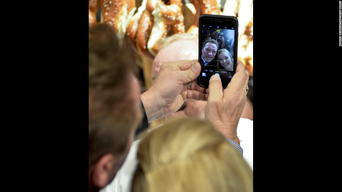 Actor Arnold Schwarzenegger and his girlfriend, Heather Milligan, take a selfie during a party in Going, Austria, on Friday, January 20. Schwarzenegger was born in Austria.