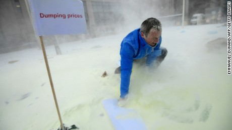 A man walks in milk powder sprayed by European Milk board (EMB) representatives in front of the European Council during a demonstration on the side of a meeting of EU ministers of agriculture, in Brussels, on January, 23, 2017. Demonstrators protested on January 23 against the European Commission's decision to gradually reinstate withdrawn milk powder stocks, in an attempt to stabilise the price, at the height of a crisis of overproduction. / AFP / EMMANUEL DUNAND        (Photo credit should read EMMANUEL DUNAND/AFP/Getty Images)