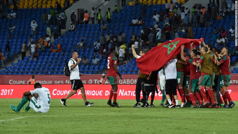 Joy and despair: Morocco's players celebrate, while the Ivory Coast's Wilfried Kanon sinks to the turf.
