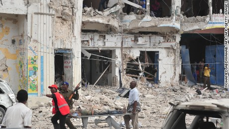 TOPSHOT - Residents carry an injured man wounded during a complex attack targeting Mogadishu hotel on 25 January 2017.  At least seven people were killed after two car bombs exploded outside a popular Mogadishu hotel on Wednesday, and gunmen forced their way inside the building and opened fire, police said / AFP / MOHAMED ABDIWAHAB        (Photo credit should read MOHAMED ABDIWAHAB/AFP/Getty Images)