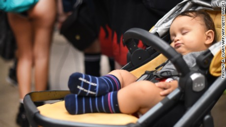 "An infant sleeps in a crib during the ""No Pants Subway Ride""  on a New York City subway platform January 10, 2016 in New York. The ""No Pants Subway Ride""  is an annual event started in 2002 by Improv Everywhere in New York, the goal  of which is for riders ride the subway train dressed in normal winter clothes without pants while keeping a straight face.  AFP PHOTO / TIMOTHY A. CLARY / AFP / TIMOTHY A. CLARY        (Photo credit should read TIMOTHY A. CLARY/AFP/Getty Images)"
