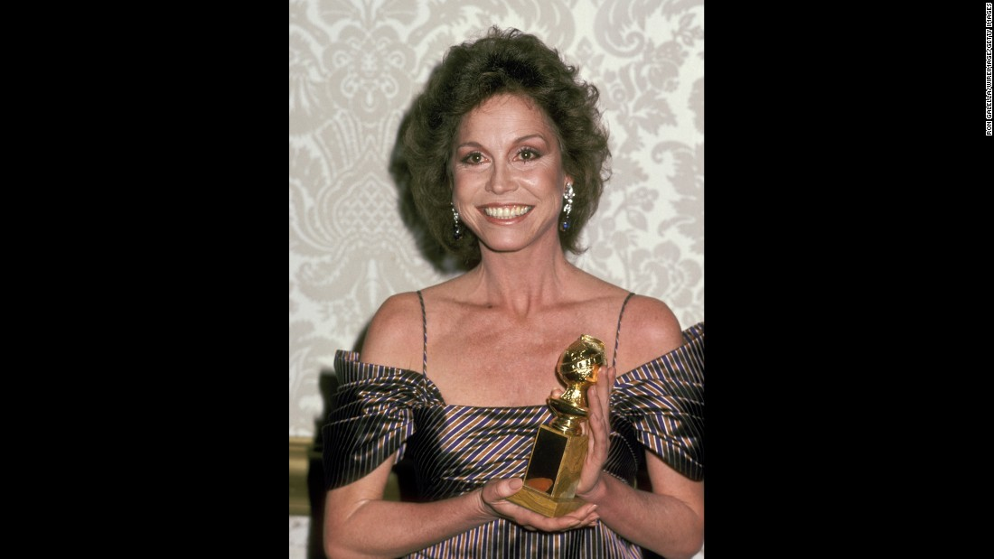 "Moore holds up the Golden Globe Award she won for ""Ordinary People."""