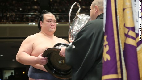 Ozeki-ranked sumo wrestler Kisenosato of Japan (L) receives the championship trophy from chairman of the Japan Sumo Association Hakkaku (R) during the awards ceremony at the end of the 15-day New Year Grand Sumo Tournament at Ryogoku Kokugikan in Tokyo on January 22, 2017. Kisenosato finished the 15-day tournament with a 14-1 record, giving him his first career tournament victory. / AFP / JIJI PRESS / JIJI PRESS / Japan OUT        (Photo credit should read JIJI PRESS/AFP/Getty Images)