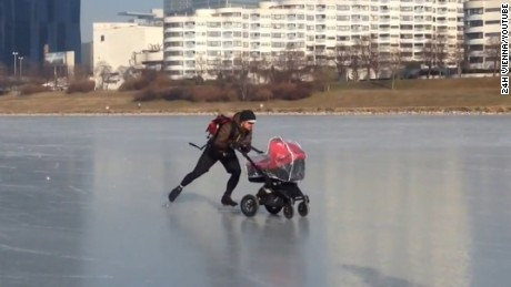 Man pushes buggy across frozen River Danube in Vienna
