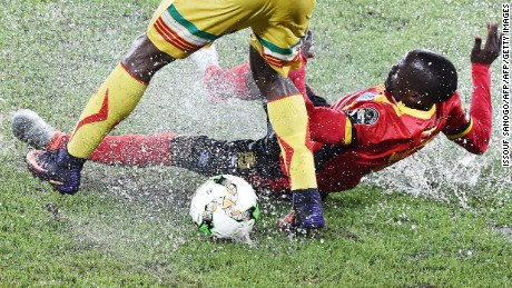 Uganda's defender Godfrey Walusimbi falls as he challenges Mali's midfielder Yves Bissouma during the 2017 Africa Cup of Nations group D football match between Uganda and Mali in Oyem on January 25, 2017. / AFP / ISSOUF SANOGO        (Photo credit should read ISSOUF SANOGO/AFP/Getty Images)