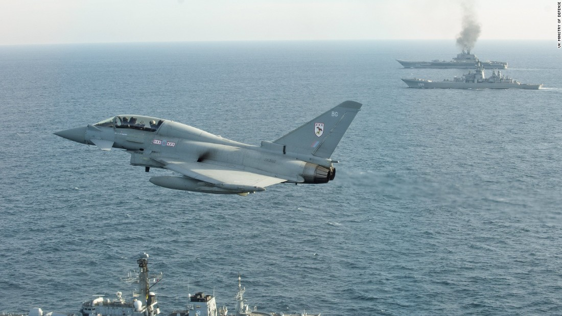 A Royal Air Force Typhoon fighter from Britain Quick Reaction Alert force flies near the Russian aircraft carrier Admiral Kuznetsov on Wednesday, January 25. The Russian carrier and a guided missile cruiser are on their way back home after participating in airstrikes in Syria.
