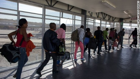 Haitian migrants seeking asylum in the United States, queue at El Chaparral border crossing in the hope of getting an appointment with US migration authorities, in the Mexican border city of Tijuana, in Baja California, on October 7, 2016. The National Human Rights Commission of Mexico (CNDH) on Saturday called on the government to support the saturated shelters and humanitarian centres for migrants in the border cities of Tijuana and Mexicali, where an increase in the arrival of Haitians and Africans hoping to be allowed to continue north to the United States has been registered. / AFP / Guillermo Arias        (Photo credit should read GUILLERMO ARIAS/AFP/Getty Images)