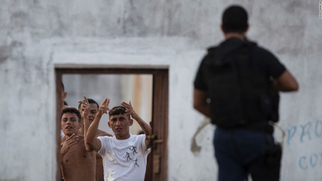 "Inmates gesture inside the Alcacuz prison in northeastern Brazil on Monday, January 23. A temporary wall was being built to separate two rival gangs <a href=""http://www.cnn.com/2017/01/14/americas/brazil-prison-riot/"" target=""_blank"">after a week of fighting</a> left dozens of inmates dead."