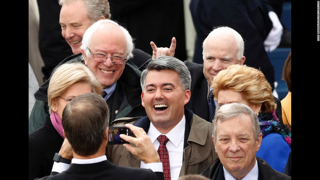 "US Sen. John McCain, back right, gives ""devil horns"" to Sen. Cory Gardner as he poses for a photo during President Trump's inauguration on Friday, January 20."