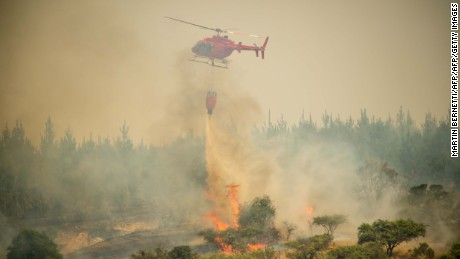A firefighter helicopter helps try to put out a forest fire in Litueche, 150 km south of Santiago, on January 24, 2017.  The Chilean government declared a state of emergency in several central areas due to forest fires that have destroyed more than 140,000 hectares of woods so far. / AFP / MARTIN BERNETTI        (Photo credit should read MARTIN BERNETTI/AFP/Getty Images)
