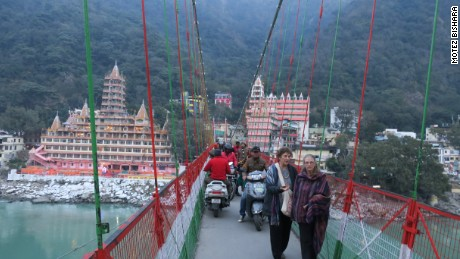 Pedestrians and motorists share a narrow path on Lakshman Jhula.