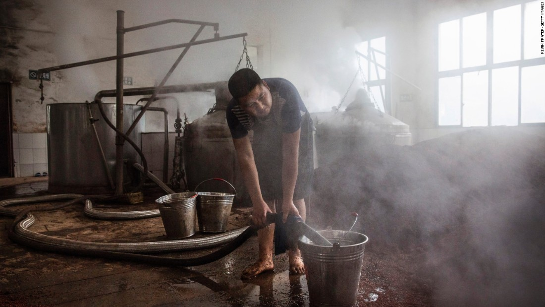 <strong>Labor intensive: </strong>A Chinese worker heats river water to be poured on the sorghum as it's prepared for fermentation.<br />