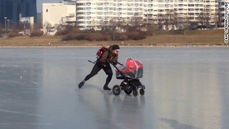 Man pushes stroller across frozen River Danube in Vienna