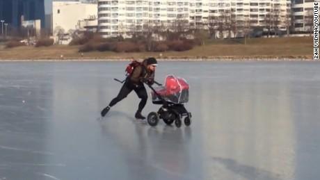 Man pushes stroller across frozen River Danube in Vienna