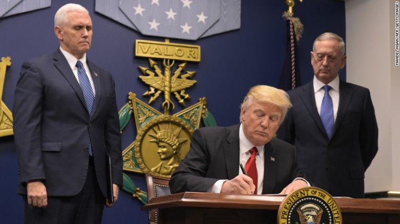 "US President Donald Trump signs an executive order alongside US Defense Secretary James Mattis and US Vice President Muike Pence on January 27, 2016 at the Pentagon in Washington, DC. Trump signed an order Friday to begin what he called a ""great rebuilding"" of the US armed services, promising new aircraft, naval ships and more resources for the military. ""Our military strength will be questioned by no one, but neither will our dedication to peace. We do want peace,"" Trump said in a ceremony at the Pentagon. / AFP / MANDEL NGAN [Photo credit should read MANDEL NGAN/AFP/Getty Images)"