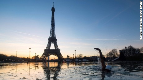TOPSHOT - A man swims in the frozen water of the Trocadero fountain in front Eiffel Tower, on January 6, 2017 in Paris.  / AFP PHOTO / OLIVIER MORINOLIVIER MORIN/AFP/Getty Images