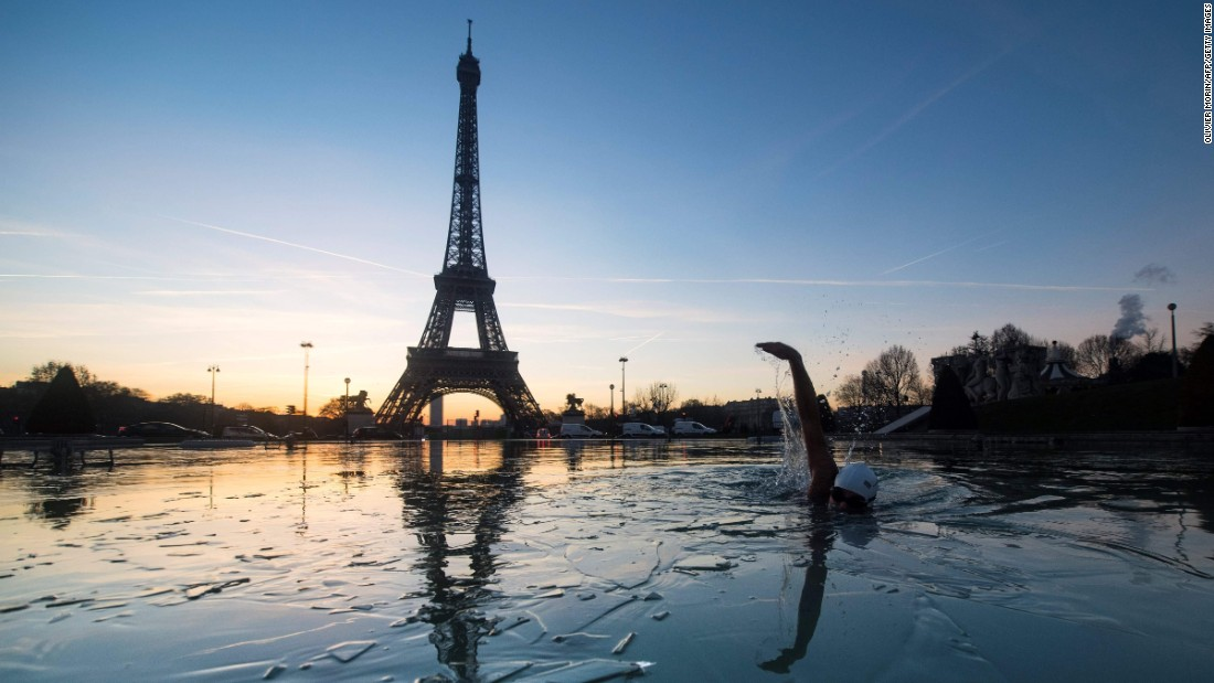 A man swims in icy water near the Eiffel Tower in Paris on Friday, January 6.