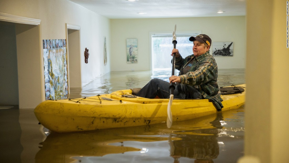 "Lorin Doeleman uses a kayak to check her flooded home in Guerneville, California, on Wednesday, January 11. <a href=""http://www.cnn.com/2017/01/09/us/us-weather/"" target=""_blank"">California and Nevada</a> were dealing with flooding, mudslides and heavy snow."