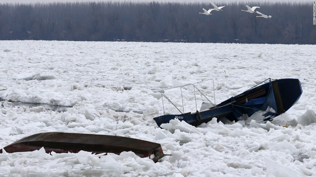 Swans fly over damaged boats on a frozen part of the Danube River in Belgrade, Serbia, on Saturday, January 14.<br />