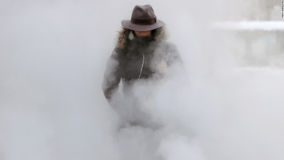 A woman walks through steam from an underground vent as temperatures dropped to minus-20 degrees Celsius (minus-4 degress Fahrenheit) in Bucharest, Romania, on Tuesday, January 10.