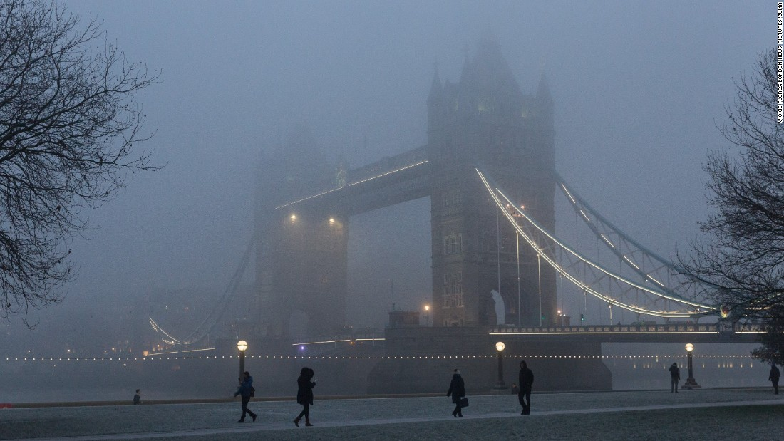 Commuters walk past London's Tower Bridge during heavy fog on Monday, January 23.<br />