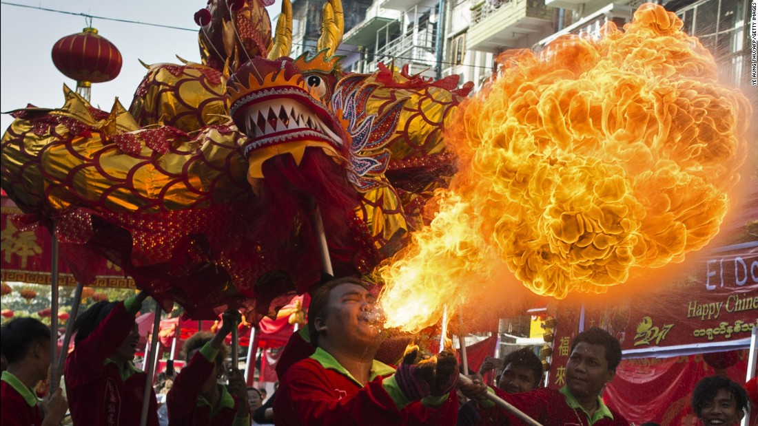 A fire-breathing man shows up the dragon behind him in Yangon, Myanmar.