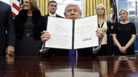 "President Donald Trump holds up a signed executive memorandum calling on the Pentagon to ""develop a comprehensive plan to defeat ISIS."""