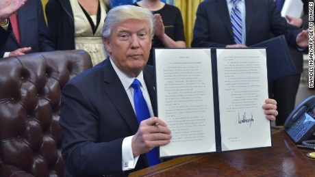 President Donald Trump holds an executive memorandum on defeating the Islamic State in Iraq and Syria after signing it in the Oval Office of the White House on January 28, 2017, in Washington, DC.