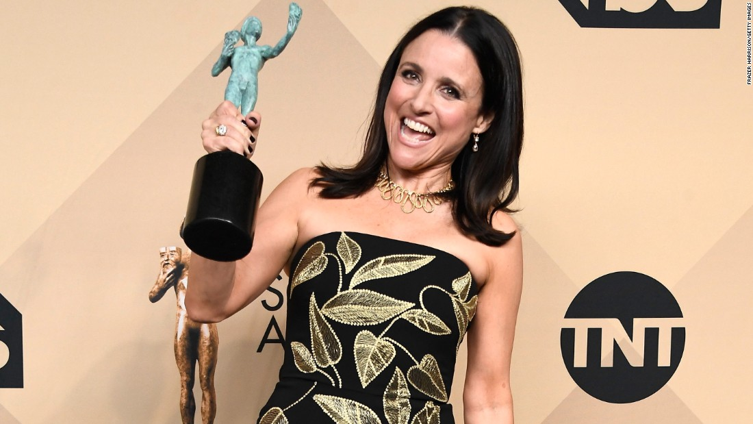 "Julia Louis-Dreyfus, the star of the show ""Veep,"" holds up the award for Outstanding Performance by a Female Actor in a Comedy Series."
