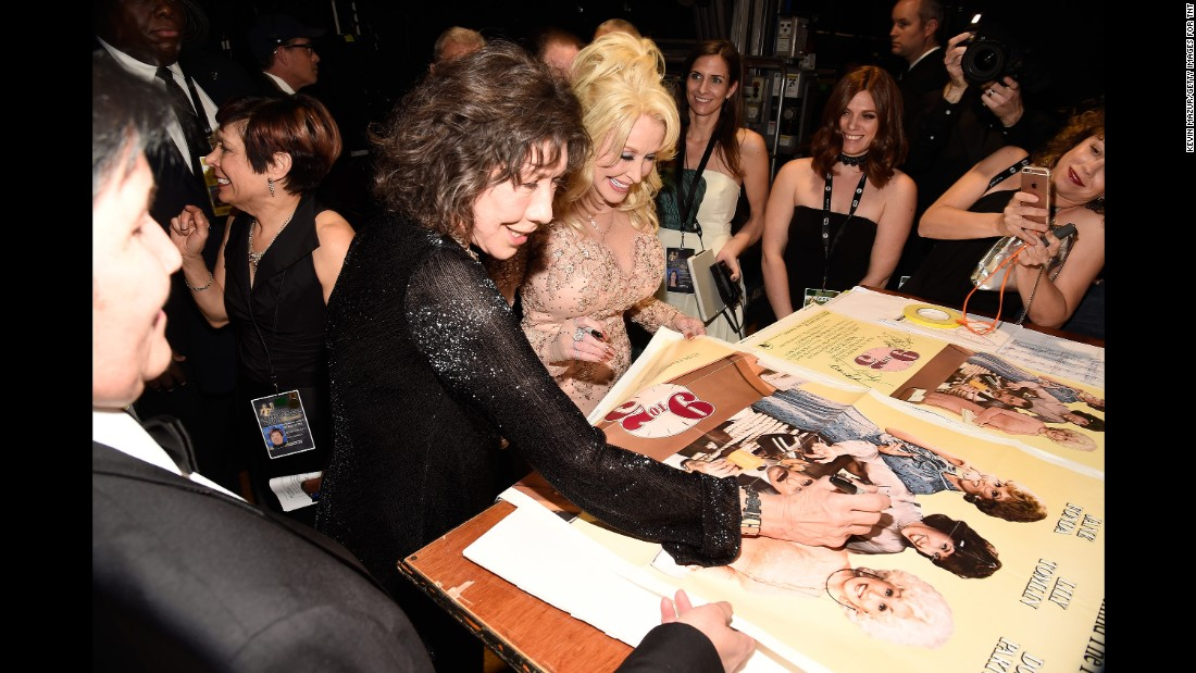 "Lily Tomlin, left, and Dolly Parton sign ""9 to 5"" posters together. During the show, Parton presented Tomlin with a Life Achievement Award."