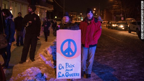 People stand with a peaceful sign near the Québec City Islamic cultural center after a shooting occurred in the mosque on Sainte-Foy Street in Quebec city on January 29, 2017.
