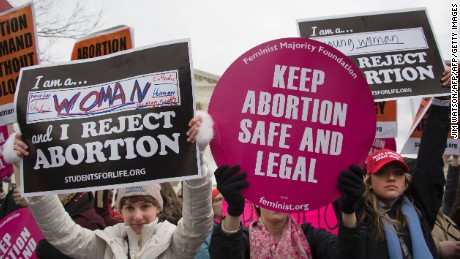 A pro-choice activist (C) demonstrates in the middle of pro-life activists as they demonstrate in front of the US Supreme Court during the March For Life in Washington, DC, January 27, 2017. Anti-abortion advocates descended on the US capital on Friday for an annual march expected to draw the largest crowd in years, with the White House spotlighting the cause and throwing its weight behind the campaign. / AFP / JIM WATSON        (Photo credit should read JIM WATSON/AFP/Getty Images)
