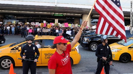 A President Trump supporter waves a US flag at Los Angeles International Airport during a demonstration Sunday over the immigration ban.