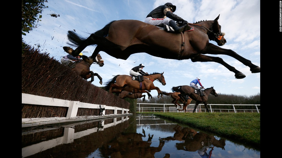 Horses clear a water jump during a race in Leicester, England, on Tuesday, January 24.