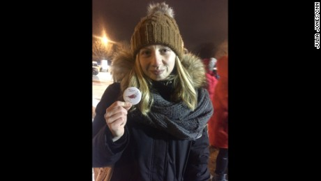 Milena Babin poses with a button from the Intercultural Center of Québec. Babin says the inscription in Arabic at the bottom means welcome to Quebec.