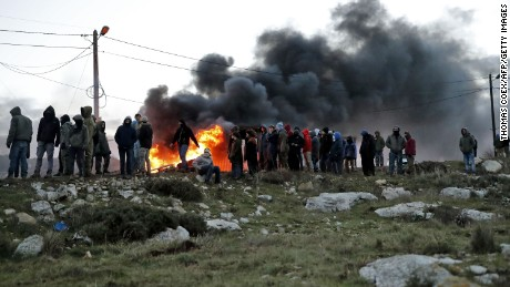 Settlers set tires ablaze at the Amona outpost as Israeli security forces prepare to evict occupants.