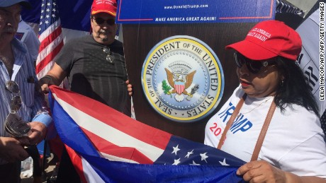 "Around 100 Cubans gather in Little Havana, around the historic Cafe Versailles, to watch the inauguration streamed in a big LCD TV installed over a pick up truck in the street on January 20, 2017 in Miami, Florida.  Weaving American and Cuban flags, and singing along a mariachi group, they chanted ""Donde estas Donald trump? en la casa Blanca!"" with a salsa rhythm. They're celebrating with beer and champagne right in the street, while the Cafe Versailles set up a table with free ""pastelitos"" in the sidewalk.   / AFP / Leila MACOR        (Photo credit should read LEILA MACOR/AFP/Getty Images)"