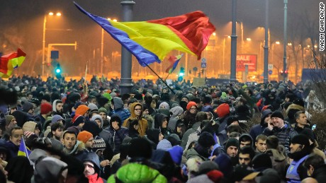 Crowds wave Romanian flags outside the government headquarters during a protest in Bucharest.
