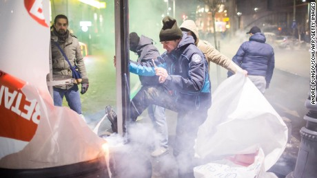 Demonstrators attack advertisements during protests in Bucharest on February 1.
