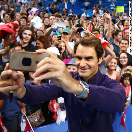 Roger Federer of Switzerland poses for a selfie with spectators after a practice session at the Perth Arena