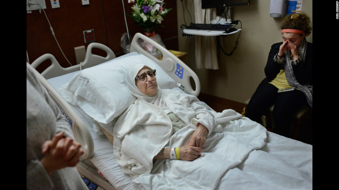 "Isaaf Jamal Eddin lies in bed as her granddaughter, Judy Ulayyet, wipes away tears at a hospital in Munster, Indiana, on Saturday, January 28. The day before, US President Donald Trump signed an <a href=""http://www.cnn.com/2017/01/28/politics/text-of-trump-executive-order-nation-ban-refugees/index.html"" target=""_blank"">executive order banning nationals of seven Muslim-majority countries</a> -- Iraq, Syria, Iran, Libya, Somalia, Sudan and Yemen -- from traveling to the US for at least the next 90 days. The executive order bans entry from those fleeing war-torn Syria indefinitely and also suspends the admission of all refugees to the United States for four months. At far left is Nour Ulayyet, Judy's mother and daughter of Eddin. Nour said her sister -- a Syrian living in Saudi Arabia -- had a valid visa to travel to the US but after arriving on Saturday, she was told at the airport that she couldn't enter to help care for their sick mother. Trump has issued a statement defending the new executive order, saying: ""We will continue to show compassion to those fleeing oppression, but we will do so while protecting our own citizens and voters."""