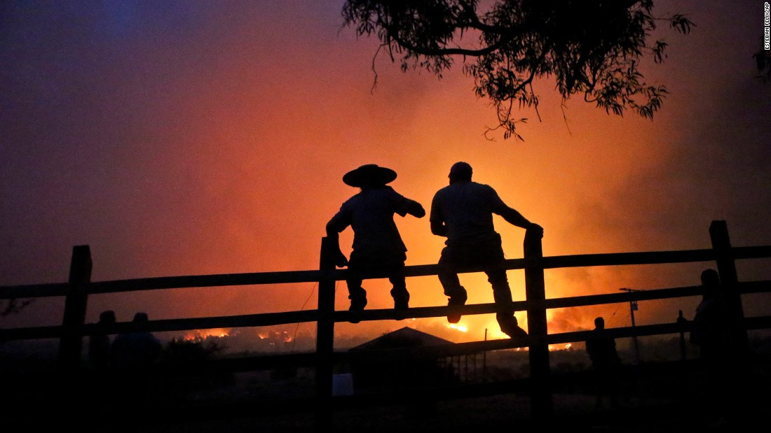 "Residents watch a forest burn in Portezuelo, Chile, on Sunday, January 29. <a href=""http://www.cnn.com/2017/01/27/americas/chile-wildfires/"" target=""_blank"">A chain of wildfires has unleashed a catastrophe in central and southern Chile</a>, killing at least 11 people, destroying thousands of homes and consuming an area about three times the size of New York City, authorities said. President Michelle Bachelet has announced that the country will continue with its various measures to deal with wild fires. ""We have never seen anything on this scale, never in the history of Chile,"" Bachelet, who has declared a state of emergency, said earlier this week."